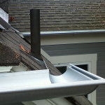 Custom residential silver gutter with a ninety degree turn flowing onto the roof