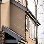 Custom fitting dark brown residential gutter and downspout for a multi level house