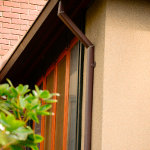 Dark brown color coordinated residential gutter and downspout for longer roof overhang